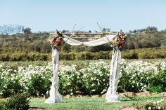 Birch Arch in Ceremony Space with fabric and two Floral Arrangements. Let's Frolic Together.