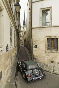 A vintage car pass thru a narrow street with de Notre Dame, on de IIe de la Cite, in Paris_ France