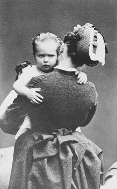 A jovem princesa Alix de Hesse nos braços de sua enfermeira, que é vista por trás. A princesa Alix olha por cima do ombro da enfermeira. Dezembro de 1873.