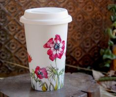 White ceramic travel mug. I'm thinking that this is a great idea for painting or decoupaging...and there's got to be a way to transfer a photo.
