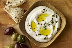 Enjoy labneh, a thick, tangy Middle Eastern yogurt, seasoned simply with crushed red pepper, black pepper and garlic, then topped with some herbs and a drizzle of good olive oil. It's a great dip for bread and veggies.