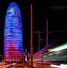 Imatge Torre Agbar il·luminada-La Torre Agbar  El monòlit cilíndric i brillant que reflecteix els colors de Barcelona s'ha guanyat un espai a la silueta de la ciutat. La Torre Agbar forma part del nostre paisatge quotidià, com la Sagrada Família o les muntanyes de Montserrat.