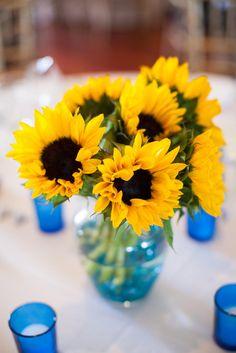 Brillantes piezas centrales de girasol amarillo en jarrones azules aqua