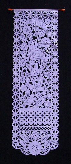 Banner; cut with chisel from tissue paper; wooden dowel at top, with purple tissue paper fringe at each end; orange tissue paper folded around banner and glued; design shows crescent moon above owl above birds. Used in Day of the Dead Festival.
