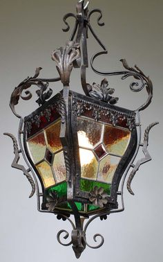 A French 19th-20th Century Baroque Revival Style Wrought-Iron and Four-Color Vitreaux Stained Glass Single-Light Hall Lantern, the rounded four stained glass panels with red, green, opaque and burgundy glass work, the scrolled wrought-iron body designed with acanthus leaves, flowers and laced details. Circa: Paris, 1900