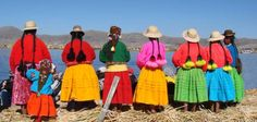 Bolivian ladies in brightly colour traditional clothing on Uros Island, Lake Titicaca.