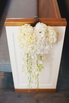 White on cream orchids with hydrangeas, AND Wod they used over the door wreath hangerz for pews, perfect!