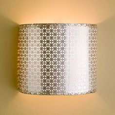 Wire Lampshade     Cut a wire lampshade frame in half and crimp aluminum radiator grille around the frame. Line the grille with opaque art paper to diffuse the light. Use a light kit to wire the light, cut off the plug, and hard-wire the sconce to the wall.        DIY Tip: Use a high-power, low-wattage LED light for long-lasting luminosity and to prevent the paper from getting too hot.
