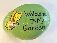 Hand-painted on River Rock. A whimsical rock for your garden, potted plant or a paper weight! This rock is painted Green with a splash of little yellow dots and a pretty yellow butterfly with the saying: Welcome To My Garden. It is sprayed with glossy spray. The back is not painted. Size: by mayra