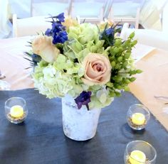 Birch vase centerpiece with green hydrangea and hypericum berries, blue thistle and delphinium, and quicksand roses.  Flowers by Eden's Echo