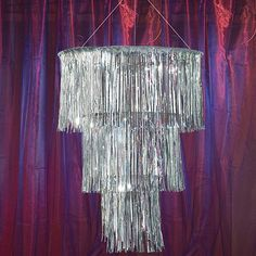 The Silver Three Tier Chandelier features thousands of shimmering metallic mylar strands. Each of the silver tier chandeliers hangs 3 long and measures 32 in diameter weighing approximately 5 pounds. The Silver Three Tier Chandelier includes a chrome chain for easy hanging. Disco Party Decorations, Prom Decor, Centerpiece Decorations, Party Themes, Disco Theme Parties, Disco Birthday Party, Girl Parties, 13th Birthday, Lampshade Chandelier