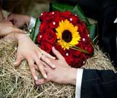 Boquet da sposa con rose rosse e girasole.