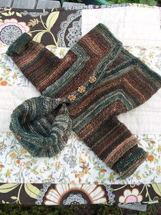 Elizabeth Zimmermann's Baby Surprise Jacket (1 year). The pattern for the jacket is published in many places, fx The Opinionated Knitter. At the link is free pattern for the hood.