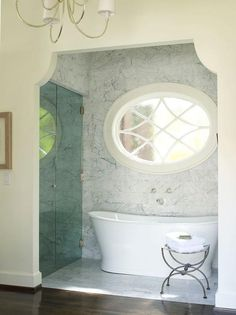 Arched bathroom nook is clad in grey and white marble filled with a freestanding tub under an oval window next to a seamless glass walk in shower illuminated by a Reed 8 Light Chandelier. Grey Bathrooms, Beautiful Bathrooms, Master Bathrooms, Bathroom Bath, Master Bedroom, Ideal Bathrooms, Master Suite, Small Bathroom, Essex Homes