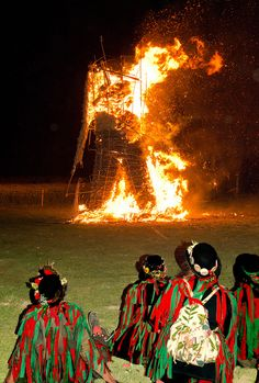 Morris dancers in traditional costume  watch the burning of the Wicker Man at  the 2011 Beltain festival held at Butser Ancient Farm by Anguskirk, via Flickr