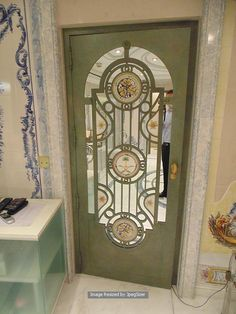 Lot 1250 - Iron door 800mm x 1950mm x 45mm with a central mirror panel and bespoke cast window grill design