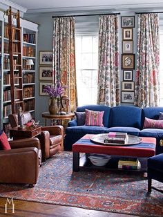 Design by Mona Hajj, potted boxwood, lots of pattern, bookcase, built in, blue couch, patterned drapes, patterned curtains