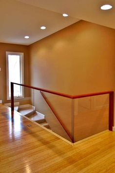 I like the glass railing. Will Need finger proof glass. A minimalist glass stair railing from a Frontenac, MO remodel. Add recess lights above stairs and window by front door.