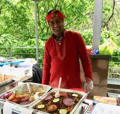 A volunteer at the Embassy of Bangladesh in Washington, DC presents traditional cuisine as part of Passport DC, a celebration of crossing cultures. (Image © Joyce McGreevy)