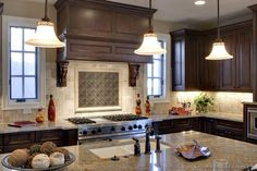 Classic wood hood with tumbled travertine and contrasting metal tile backsplash  (Kitchen-Design-Ideas.org)