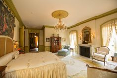Traditional Master Bedroom with Wainscoting, Carpet, Crown molding, Chandelier, High ceiling, Wall sconce, Cement fireplace