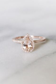Diamond Wedding Rings A Pear Shaped Diamond Engagement Ring With Halo Diamonds Sits On A Marble Table. - Engagement ring shopping is both one of the best things -- and one of the worst. See why in this post, and my picks of the prettiest rings. Top Engagement Rings, Engagement Ring Settings, Diamond Shaped Engagement Ring, Wedding Engagement, Rose Gold Engagement Ring, Vintage Inspired Engagement Rings, Engagement Ring Shapes, Engagement Jewelry, Ring Rosegold