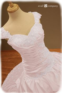 Blush Pink Wedding Dress - Angela Style - Avail & Company, LLC  This gorgeous dress is made of blush pink matte satin with a drop waist and ruched bodice. The dress displays bead work(clear beads and pearls) and lace. The back features corset styled lacing. The dress also features detachable straps and a detachable train.