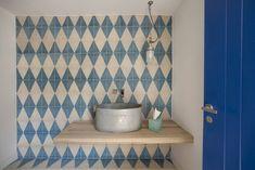 A bathroom with blue triangle tiles from the Sybilla collection, a collaboration with fashion designer Sybilla Sorondo.