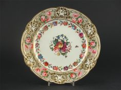 A good London decorated Nantgarw plate, with flower and scroll moulded borders, brightly enamelled with fruit, flowers and insects, probably by Robins and Randall, encircled by a garland, the border with pink roses and leaves on a gilt dot ground, 'Nantgarw CW' impressed, c.1820, 25cm. Provenance: The Major Guy Dawnay Collection. Cf. E Morton Nance pl.CLXX for a similar plate.