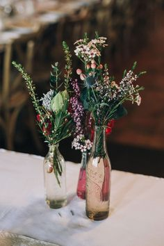 wildflower wedding centrepiece in mixed vintage bottles | Raconteur Photography