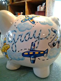 Every Personalized Piggy Bank in my shop is Handpainted and includes free personalization. Sorry to disappoint you but i can no longer guarantee delivery for Holiday orders. !Personalized Piggy Bank Airplane Design Primary Colors Boys Room Handpainted  A great airplane design to match primary colors in your fly boys room. Up, up and away!! Please remember that if you have bedding and special colors that youd like me to match and design on a bank, it will be my pleasure.  These wonderful hand…