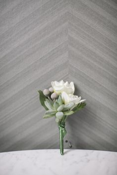 The boutonnieres will be a combination of pale green succulents and purple freesia wrapped in a band of ribbon.