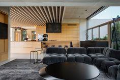 faux plafond bois, lambris mural assorti, canapé d'angle noir, table ronde noir mat et tapis gris anthracite