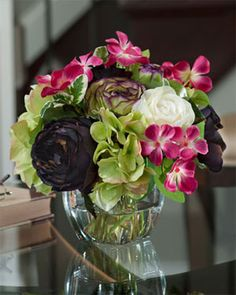 """Ranunculus & Hydrangea Accent    Item Number: FLA711-MS     Price $69.00       •9""""H x 9""""W   •Lifelike Hydrangea Blossoms   •Tapered Glass Vase    Ranunculus and hydrangea enhanced with cheerful catharanthus make this a very happy bouquet. Set with acrylic water in a 3-1/2"""" tapered square glass vase, it's a perfect way to send a little joy to someone special."""