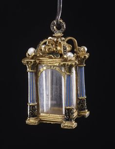 Lantern-shaped pendant reliquary; gold; middle formed of square tube of rock crystal with column at each corner, enamelled; bottom with quatrefoil; beneath, four enamel scrolls, pearl at termination of each; date engraved on one side. Origin: Uncertain, traditionally attributed to a German workshop in the late 16th century but probably of 19th-century manufacture.