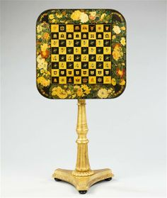 England, circa 1830  An early 19th century tilt-top painted chess table, the board is enriched with armorial motifs surrounded by an elaborate naturalistically painted foliate border. The top rises to reveal a hidden games compartment and is supported on a giltwood column stem standing on a tripod plinth terminating in pad feet
