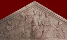 """Relief of the Fates from a sarcophagus for a woman, with a kneeling man on either side beseeching mercy. Detail: Clotho, on the left, holds a distaff and spindle with which she spins the thread of life; Lachesis, in the center, holds a scale for weighing the thread of life and the cornucopia of Fortuna/Tyche; Atropos, on the right, holds an open scroll, probably symbolizing """"the book of fate."""" Mid-2nd century CE. Rome, Palazzo Nuovo (Capitoline Museums)."""