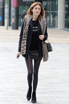Alexa Chung accessorised her leather mini skirt, Bella Freud jumper and navy coat with a herringbone and leopard-print scarf.