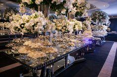Mesa espelhada com doces deliciosas e arranjos de flor