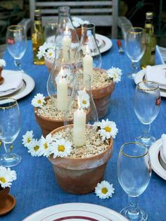 Daisies and denim: Dark blue denim serves as a table runner for this casual dinner. Terra cotta pots hold chimneys and candles that seem to grow from the pebbles. Tiny pots of daisies sit atop individual plates.