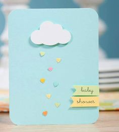 """These simple shower invitations look great -- and only take a few minutes to make! Fold a light blue piece of scrapbook paper in half, and round the corners with a corner rounder tool. Make a cloud shape with a paper punch and adhere using adhesive foam. Punch small hearts from different colors of paper and adhere below the cloud for raindrops. Write """"baby shower"""" on strips of colored paper; adhere to the bottom right-hand corner of the card using adhesive foam for a dimensional effect./"""