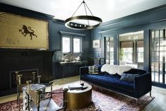 Despite its size, the living room doesn't receive a lot of natural light, so Norris created a cozy atmosphere. The cobalt-blue velvet Room & Board sofa elevates the space, while the two leather campaign chairs she sourced on 1stdibs lend a masculine touch. Accessories such as an antique Heriz rug, an all-bronze drum cocktail table from Design Within Reach, and an antique colonial flag above the fireplace add both sophistication and whimsy.