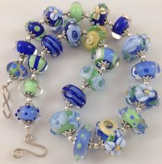 Blues and Greens on this necklace, coated in super crystal Clear Glass. Lots of Flowers , Spots , Stripes .