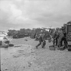 3rd Division troops sheltering behind Universal Carriers (one with a towed 6-pdr AT gun) on Queen beach, Sword area, 6 June 1944