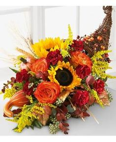 This horn-shaped basket of the Better Homes and Gardens Horn of Plenty Bouquet from Avas Flowers is gorgeously adorned with sunflowers, bi-colored orange roses and burgundy carnations seated amongst eucalyptus and wheat to create the perfect centerpiece for your Thanksgiving feast.
