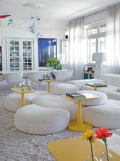 Entre o mar de brancos do apartamento do arquiteto David Bastos, destacam-se as mesas de apoio amarelas, design de Paola Navone. Todo o resto é como a neve: módulos, tapete, paredes, cortina, mesa de jantar e cadeiras