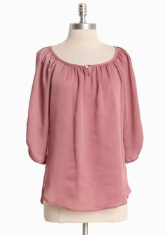 """Garden Aura Silky Blouse 28.99 at shopruche.com. Perfected with a silky sheen, this dusty pink blouse is accented with feminine details and a scooped hemline.  100% Polyester, Made in USA, 27"""" length from top of shoulder"""