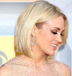 Carrie Underwood in a gold dress on the red carpet at the 2016 Academy of Country Music Awards held at the MGM Grand Garden Arena in Las Vegas on April 3, 2016