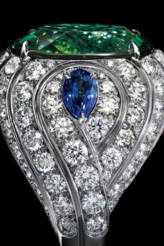 An elaborate setting of swirling diamonds and sapphires in platinum embrace a stunning 16.61-carat oval green tourmaline.