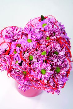 Can you feel my heart beat? For the shy admirer who wants to make a subtle statement on Valentine's Day or before a promising date: a subtle heart of flowers made up of beautifully marked pink striped chrysanthemums, playfully decorated with red thread. A piece of wire at the centre can work wonders in retaining the shape: arrange one layer of flowers around it and it will be impossible to spot.
